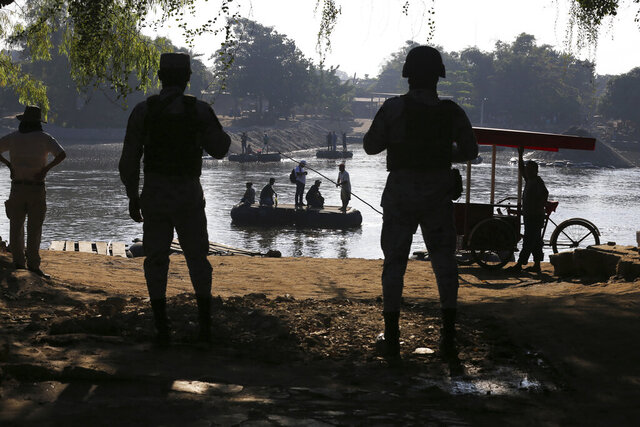 """Mexican National Guards stand watch over the Suchiate River where locals transport cargo and ferry people between Mexico and Guatemala, near Ciudad Hidalgo, Mexico, Friday, Jan. 24, 2020, a location popular for Central American migrants to cross from Guatemala to Mexico. One National guard said it's easy to distinguish local Guatemalans who cross for ordinary workday reasons for their manner of speaking, and they're welcome """"because they're neighbors."""" (AP Photo/Marco Ugarte)"""
