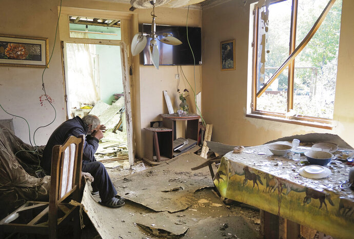 Yury Melkonyan, 64, sits in his house damaged by shelling from Azerbaijan's artillery during a military conflict in Shosh village outside Stepanakert, the separatist region of Nagorno-Karabakh, Saturday, Oct. 17, 2020. The latest outburst of fighting between Azerbaijani and Armenian forces began Sept. 27 and marked the biggest escalation of the decades-old conflict over Nagorno-Karabakh. The region lies in Azerbaijan but has been under control of ethnic Armenian forces backed by Armenia since the end of a separatist war in 1994. (AP Photo)
