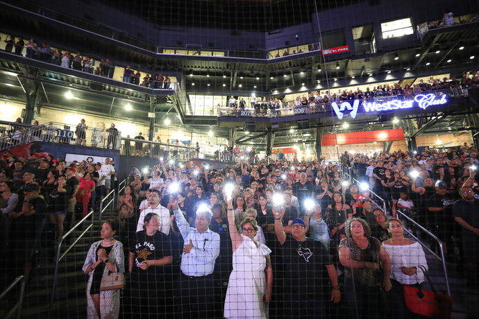 People hold up their cellphones as the names of the victims of the Aug. 3 mass shooting are read during a memorial service, Wednesday, Aug. 14, 2019, at Southwest University Park, in El Paso, Texas. (AP Photo/Jorge Salgado)