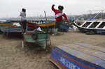A boy jumps amid boats as he plays with other children on the second to last day of the government-mandated lockdown put in place to curb the spread of the new coronavirus, at a dock at Pescadores beach in Lima, Peru, Monday, June 29, 2020. (AP Photo/Martin Mejia)