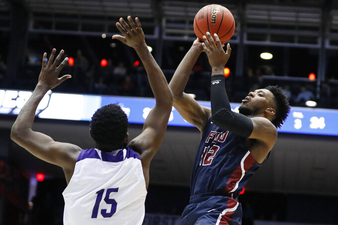 Fairleigh Dickinson's Kaleb Bishop (12) shoots over Prairie View A&M's Gerard Andrus (15) during the first half of a First Four game of the NCAA college basketball tournament, Tuesday, March 19, 2019, in Dayton, Ohio. (AP Photo/John Minchillo)