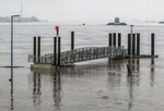 A barge and small boat make their way along the Ohio River as the river's high level raises the boarding dock away from shore at English Park, Wednesday, Feb. 20, 2019, in Owensboro, Ky. (Greg Eans/The Messenger-Inquirer via AP)