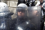 Riot police officers stand guard in front of the Serbian presidency building in Belgrade, Serbia, Sunday, March 17, 2019. As Serbian president Aleksandar Vucic held a news conference in the presidency building in downtown Belgrade, thousands of opposition supporters gathered in front demanding his resignation. Skirmishes with riot police were reported, including officers firing tear gas against the protesters who have pledged to form a human chain around the presidency to prevent Vucic from leaving the building. (AP Photo/Marko Drobnjakovic)