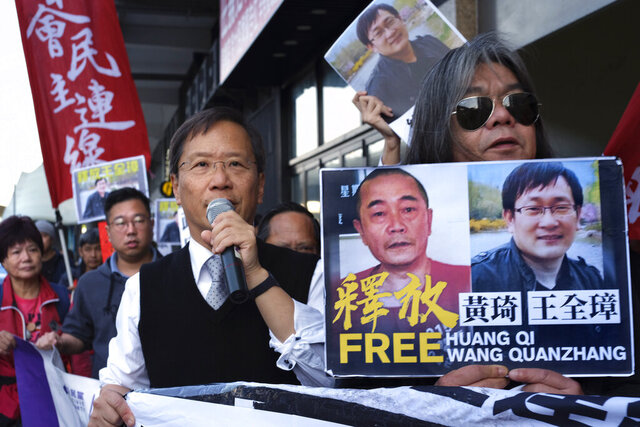 FILE - In this Jan. 29, 2019, file photo, protesters demonstrate in support of prominent Chinese human rights lawyer Wang Quanzhang, right on poster, outside the Chinese liaison office in Hong Kong. Wang was released from prison Sunday, April 5, 2020, after being held for more than four years, his wife Li Wenzu said. Wang was among more than 200 lawyers and legal activists swept up in 2015 in what became known as the 709 Crackdown for the date, July 9, when most of them were detained.(AP Photo/Vincent Yu, File)