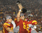 FILE - In this Jan. 1, 2009, file photo, Southern California quarterback Mark Sanchez (6) holds up the trophy as he celebrates with teammates Kaluka Maiava, left, and Damian Williams (18) after USC beat Penn State 38-24 in the Rose Bowl NCAA college football game, in Pasadena, Calif. Former USC star and New York Jets first-round pick Mark Sanchez is retiring from the NFL and joining ESPN as a college football analyst. (AP Photo/Mark J. Terrill, File)