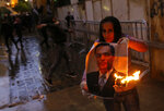 An anti-government protester burns a picture of new Lebanese Prime Minister Hassan Diab during ongoing protests in Beirut, Lebanon, Wednesday, Jan. 22, 2020.  Lebanon's new government held its first meeting Wednesday, a day after it was formed following a three-month political vacuum, with the prime minister saying his Cabinet will adopt financial and economic methods different than those of previous governments.  (AP Photo/Bilal Hussein)