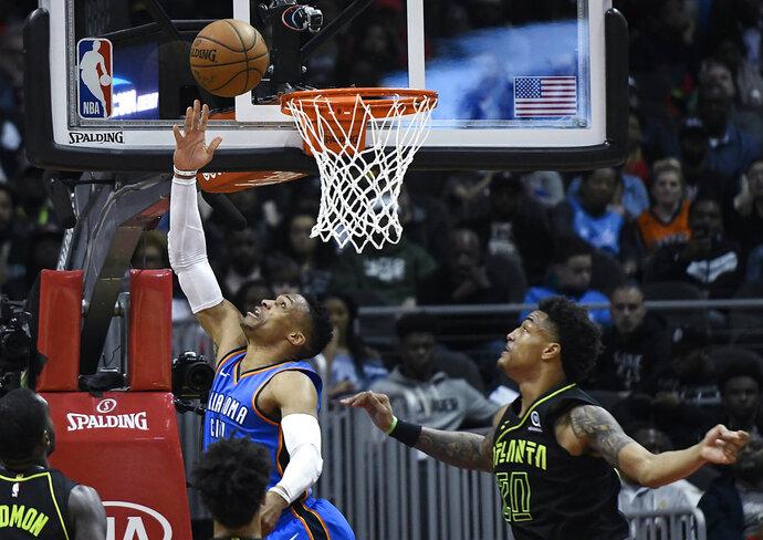 Oklahoma City Thunder guard Russell Westbrook shoots a reverse layup as Atlanta Hawks forward John Collins (20) defends during the first half of an NBA basketball game, Tuesday, March 13, 2018, in Atlanta. (AP Photo/John Amis)