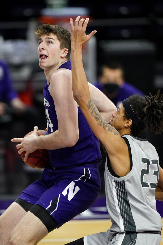 Northwestern center Matthew Nicholson, left, drives to the basket against Chicago State forward Jordan Polynice during the second half of an NCAA college basketball game in Evanston, Ill., Saturday, Dec. 5, 2020.  (AP Photo/Nam Y. Huh)