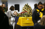A woman lays flowers in tribute to a flight crew member of the Ukrainian 737-800 plane that crashed on the outskirts of Tehran, during a memorial service at Borispil international airport outside Kyiv, Ukraine, Sunday, Jan. 19, 2020. An Ukrainian passenger jet carrying 176 people crashed just minutes after taking off from the Iranian capital's main airport on Jan. 8, 2020. (AP Photo/Efrem Lukatsky)
