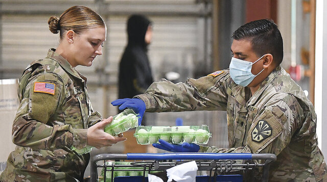 U.S. Army Arizona National Guard Spc. Jordyn VanWormer, left, and Spc. Angel Lopez load eggs into a shopping cart inside Yuma Community Food Bank, early Friday morning, Dec. 4, 2020, in Yuma, Aiz. It was the Guard's last day working at the Food Bank. Soldiers had been assisting with serving the needs of Yumans since April during the COVID-19 pandemic. (Randy Hoeft/The Yuma Sun via AP)