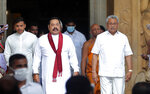 Sri Lanka's former President Mahinda Rajapaksa, center, leaves with his younger brother, President Gotabaya Rajapaksa, right, after being sworn in as the prime minister at Kelaniya Royal Buddhist temple in Colombo, Sri Lanka, Sunday, Aug. 9, 2020. (AP Photo/Eranga Jayawardena)