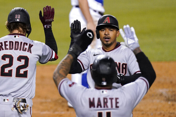 Arizona Diamondbacks' Eduardo Escobar, upper right, is congratulated by Ketel Marte, lower right, and Josh Reddick after hitting a two-run home run during the sixth inning of a baseball game Thursday, May 20, 2021, in Los Angeles. (AP Photo/Mark J. Terrill)