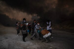 Refugees and migrants carrying their belongings flee a fire burning at the Moria camp on Lesbos island, Greece, Wednesday, Sept. 9, 2020. Moria camp's life ended as it began, in drama: Successive fires that started before dawn on Sept. 9 devastating the site and making 12,000 inhabitants homeless during a COVD-19 lockdown.(AP Photo/Petros Giannakouris)