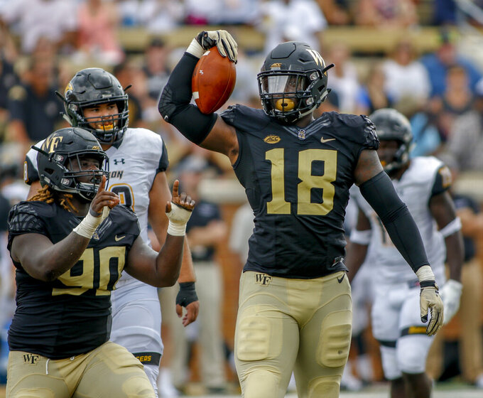 FILE - In this Sept. 9, 2018, file photo, Wake Forest defensive linemen Carlos Basham Jr. (18) and Sulaiman Kamara celebrate after sacking Towson quarterback Tom Flacco in the first half of an NCAA college football game, in Winston-Salem, N.C. Basham was selected to The Associated Press All-Atlantic Coast Conference football team, Tuesday, Dec. 10, 2019. (AP Photo/Nell Redmond, File)