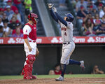 Houston Astros' George Springer, right, celebrates his solo home run as Los Angeles Angels catcher Dustin Garneau waits during the third inning of a baseball game in Anaheim, Calif., Thursday, July 18, 2019. (AP Photo/Kyusung Gong)