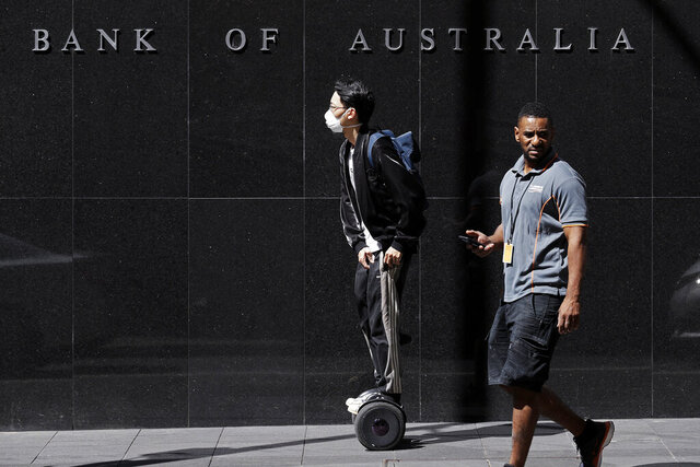 FILE - In this March 19, 2020, file photo, a man wearing a mask, left, rides a personal transporter past the Reserve Bank of Australia in Sydney. The coronavirus pandemic pushed Australia's economy into recession for the first time in 29 years in the first quarter of the year 2022, and the situation is expected to get worse.  (AP Photo/Rick Rycroft, File)