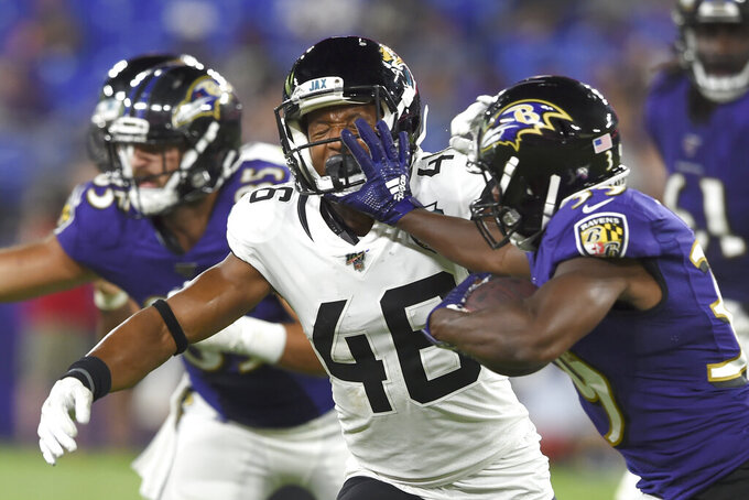 Baltimore Ravens running back Tyler Ervin, right, fends off  Jacksonville Jaguars' Josh Robinson during the second half of an NFL football preseason game Thursday, Aug. 8, 2019, in Baltimore. The Ravens won 29-0. (AP Photo/Gail Burton)