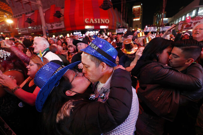FILE - In this Jan. 1, 2018, file photo, newlyweds Alison and Kenny Finchum, lower left, of Tulsa, Okla., kiss just after midnight during a New Year's party at the Fremont Street Experience in downtown Las Vegas. Plans for a 14,000-person New Year's Eve street party at canopied casino-mall in Las Vegas are facing pushback from state and local officials, who worry Nevada hospitals may not be able to withstand a potential