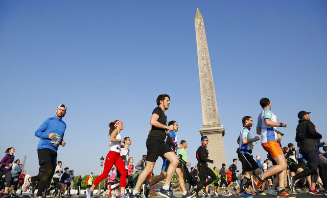 FILE  - In this Sunday, April 14, 2019 file photo, competitors in the Paris Marathon run past the Cleopatra's Needle at the Place de la Concorde in Paris, France.  The Paris Marathon has been canceled because of the coronavirus after repeated attempts to find a new date, organizers said Wednesday, Aug. 12, 2020. The race was originally due to take place in April but was then moved to October. Organizers said they'd recently tried to rearrange the race for November but continuing travel restrictions made that unrealistic. (AP Photo/Thibault Camus, File)