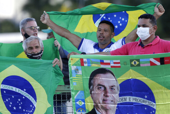 Demonstrators show their support for Brazil's President Jair Bolsonaro in front of the Planalto presidential palace, in Brasilia, Brazil, Monday, March 29, 2021. President Bolsonaro has undertaken a cabinet reshuffle underscored by recent turmoil in his administration, and who has seen his approval ratings slide this year amid a raging new coronavirus pandemic that has taken the lives of more than 300,000 Brazilians. (AP Photo/Eraldo Peres)