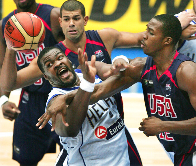 FILE - In this Sep. 1, 2006, file photo, Greece's Sofoklis Schortsiantis, left, drives to the basket as USA's Dwight Howard (12), right, NBA's Orlando Magic, and Shane Battier, of NBA's Memphis Grizzlies, ceneter back, guard during the semifinals of the World Basketball Championships in Saitama, Japan. The 2006 world championship was perhaps the last truly wide-open international basketball event. Argentina arrived as the Olympic champion and Spain left as the world champion, the last time for a long while anyone other than the U.S. would hold either title. (AP Photo/Itsuo Inouye, File)