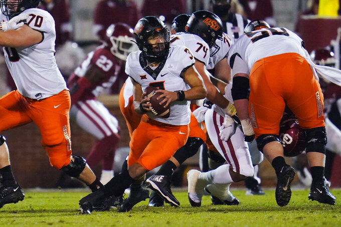 Oklahoma State quarterback Spencer Sanders scrambles during the second half of the team's NCAA college football game against Oklahoma in Norman, Okla., Saturday, Nov. 21, 2020. (AP Photo/Sue Ogrocki)