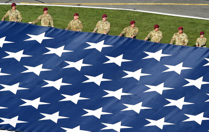 Soldiers hold a large United States flag during activities before a NASCAR Cup Series auto race at Charlotte Motor Speedway in Concord, N.C., Sunday, May 26, 2019. (AP Photo/Mike McCarn)