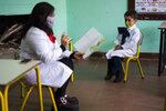 FILE - In this Monday, June 1, 2020 file photo a student wearing a face mask amid the coronavirus pandemic pays attention to his teacher at a rural school near Empalme Olmos, Uruguay. Countries with the least corruption have been best positioned to weather the health and economic challenges of the coronavirus pandemic, according to a closely-watched annual study released Thursday by anti-graft watchdog organization, Transparency International. Uruguay scored 71 _ putting it at 21st place on the list. It invests heavily in health care and has a strong epidemiological surveillance system, which has helped not only with COVID-19 but also other diseases like yellow fever and Zika, Transparency said. (AP Photo/Matilde Campodonico, file)