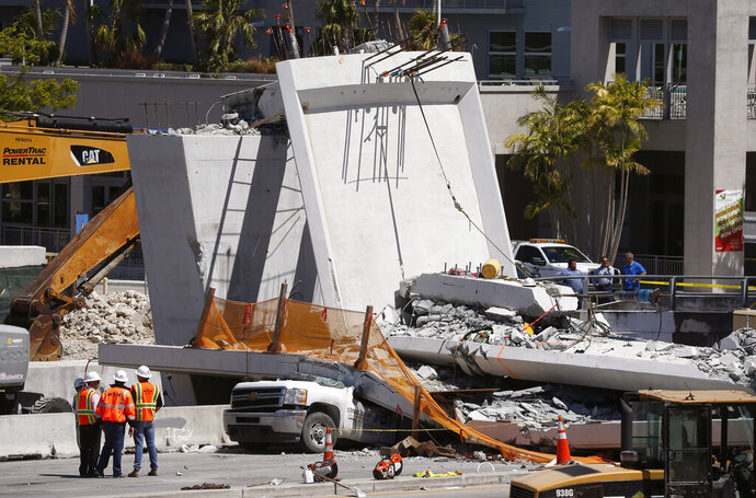 FILE- In this March 16, 2018 file photo, workers stand next to a section of a collapsed pedestrian bridge near Florida International University in Miami. National Transportation Safety Board officials concluded on Tuesday, Oct. 22, 2019, that the Miami university bridge that collapsed and killed six people showed significant design errors and the state government should have conducted greater oversight (AP Photo/Wilfredo Lee, File)