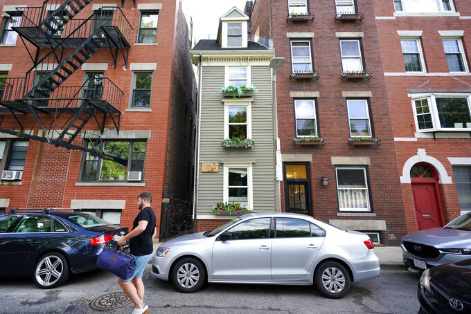 """FILE— In this Aug. 13, 2021 file photograph, a man walks by Boston's famous Skinny House, at center, after it was listed for sale for $1.2 million. The sale of the home was closed Thursday Sept. 16, 2021 for $1.25 million, according to Zillow. The home """"received multiple offers and went under agreement for over list price in less than one week,"""" real estate agency CL Properties posted on Facebook.   (AP Photo/Elise Amendola, File)"""