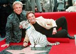 FILE - Illusionists Siegfried Fischbacher, left and Roy Uwe Ludwig Horn pose for photographers with a white tiger cub after they unveiled their star on the Hollywood Walk of Fame in Los Angeles, Calif., on Sept. 23, 1994. German news agency dpa is reporting that Fischbacher, the surviving member of duo Siegfried & Roy has died in Las Vegas at age 81. The news agency said Thursday that Fischbacher's sister, a nun who lives in Munich, confirmed his death of cancer. Fischbacher's long-time show business partner, Roy Horn, died in May of complications from COVID-19 at a Las Vegas hospital. (AP Photo/Neil Jacobs, File)