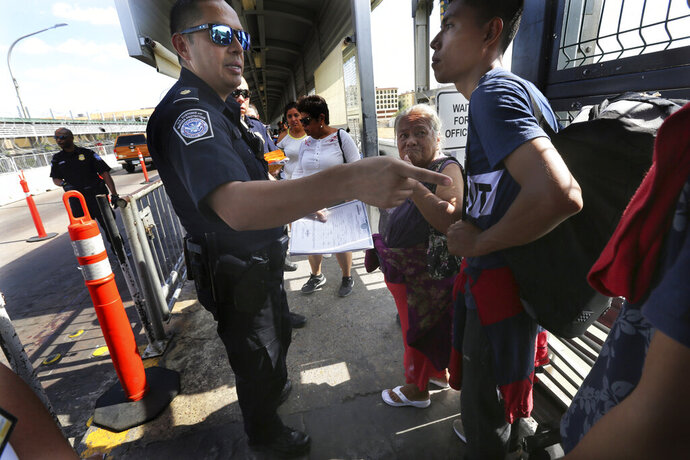 A United States Customs and Border Protection Officer checks the documents of migrants, before being taken to apply for asylum in the United States, on the International Bridge 1 in Nuevo Laredo, Mexico, Wednesday, July 17, 2019. Asylum-seekers grappled to understand what a new U.S. policy that all but eliminates refugee claims by Central Americans and many others meant for their bids to find a better life in America amid a chaos of rumors, confusion and fear. (AP Photo/Marco Ugarte)