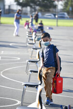 A masked student waits to be taken to his classroom on the first day of school at Enrique S. Camarena Elementary School, Wednesday, July 21, 2021, in Chula Vista, Calif. The school is among the first in the state to start the 2021-22 school year with full-day, in-person learning. (AP Photo/Denis Poroy)