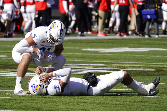 San Jose State quarterback Nick Starkel lies on his back after getting hit by Jacob Songer (61) in the first half of the Arizona Bowl NCAA college football game against Ball State, Thursday, Dec. 31, 2020, in Tucson, Ariz. (AP Photo/Rick Scuteri)