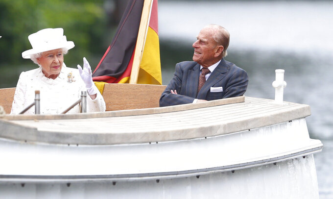 FILE - In this Wednesday June 24, 2015 file photo, Britain's Queen Elizabeth II and Prince Philip travel by boat on the Spree river in Berlin, Germany. Buckingham Palace officials say Prince Philip, the husband of Queen Elizabeth II, has died, it was announced on Friday, April 9, 2021. He was 99. Philip spent a month in hospital earlier this year before being released on March 16 to return to Windsor Castle. Philip, also known as the Duke of Edinburgh, married Elizabeth in 1947 and was the longest-serving consort in British history.  (Hannibal Hanschke/Pool Photo via AP, File)
