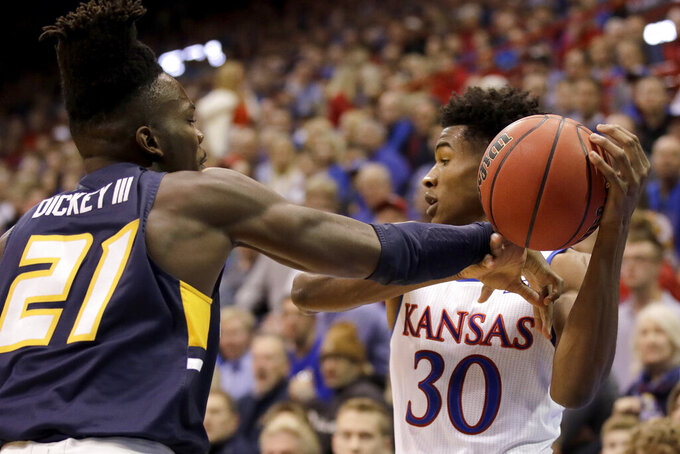 UNC Greensboro's James Dickey (21) tries to steal the ball from Kansas' Ochai Agbaji (30) during the first half of an NCAA college basketball game Friday, Nov. 8, 2019, in Lawrence, Kan. (AP Photo/Charlie Riedel)