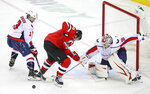 Washington Capitals defenseman Nick Jensen (3) swats the puck away from New Jersey Devils left wing Miles Wood (44) as they battle in front of Capitals goalie Ilya Samsonov (30) during the second period of an NHL hockey game Sunday, Feb. 28, 2021, in Newark, N.J. (Andrew Mills/NJ Advance Media via AP)