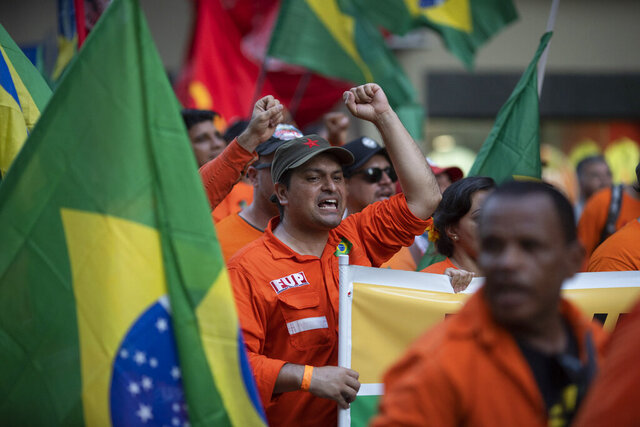 Oil workers march during a protest against layoffs at state oil company Petrobras in Rio de Janeiro, Brazil, Tuesday, Feb. 18, 2020. Brazilian oil workers and oil giant Petrobras were locked in a power struggle Tuesday over the company's privatization plans, with the union saying thousands of employees are on an indefinite strike. (AP Photo/Silvia Izquierdo)