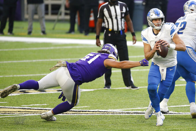 Detroit Lions quarterback Matthew Stafford (9) runs from Minnesota Vikings defensive tackle Hercules Mata'afa, left, during the second half of an NFL football game, Sunday, Nov. 8, 2020, in Minneapolis. (AP Photo/Bruce Kluckhohn)