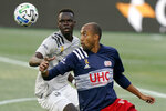 Montreal Impact's Karifa Yao, left, and New England Revolution's Teal Bunbury, right, keep their eyes on the ball during the first half of an MLS soccer match, Wednesday, Sept. 23, 2020, in Foxborough, Mass. (AP Photo/Steven Senne)