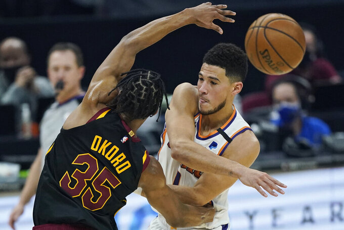 Phoenix Suns' Devin Booker, right, passes against Cleveland Cavaliers' Isaac Okoro in the first half of an NBA basketball game, Tuesday, May 4, 2021, in Cleveland. (AP Photo/Tony Dejak)