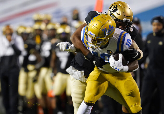 UCLA running back Demetric Felton, front, is tackled by Colorado linebacker Akil Jones after catching a pass in the first half of an NCAA college football game Saturday, Nov. 7, 2020, in Boulder, Colo. (AP Photo/David Zalubowski)