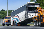 A bus is towed away after a collision with the bus and a tractor-trailer on the New Jersey Turnpike, Wednesday, July 11, 2018 in Hamilton Township, N.J.  The crash occurred early Wednesday in the truck lanes of the highway between interchanges 7 and 7A in Hamilton Township, not far from Trenton. State police say roughly 50 people were aboard the bus, which had severe front-end damage. The tractor-trailer also was damaged in the crash. (Michael Mancuso/NJ Advance Media via AP)