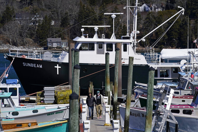 Marc Nighman and Jonathan Partin leave the Sunbeam after receiving a COVID-19 vaccination, Friday, March 19, 2021, in Northeast Harbor, Maine. The 74-foot vessel operated by the non-profit Maine Seacoast Mission, seen in the background, has vaccinated hundreds of islanders. (AP Photo/Robert F. Bukaty)