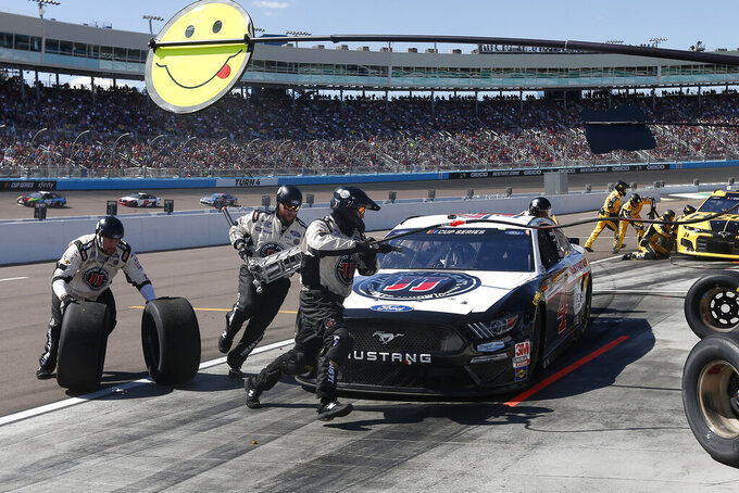 The pit crew for Kevin Harvick races around his car after changing right side tires on lap 76 of a NASCAR Cup Series auto race at Phoenix Raceway, Sunday, March 8, 2020, in Avondale, Ariz. (AP Photo/Ralph Freso)