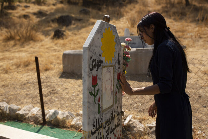 In this Sept. 13, 2019 photo, Layla Taloo visits the grave of a Yazidi woman who took her own life after she was captured by Islamic State militants in Mosul, buried on a hill overlooking the Lalish shrine in northern Iraq. Some 3,500 slaves have been freed from IS' clutches in recent years, most of them ransomed by their families. But more than 2,900 Yazidis remain unaccounted for, including some 1,300 women and children, according to the Yazidi abductees office in Iraq's Kurdish autonomous region. (AP Photo/Maya Alleruzzo)
