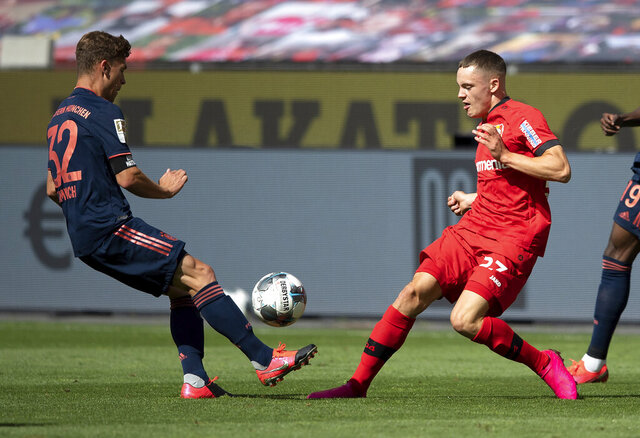 Florian Wirtz of Leverkusen, right, is challenged by FC Bayern Munich's  Joshua Kimmich during the German Bundesliga soccer match between Bayer Leverkusen and Bayern Munich in Leverkusen, Germany, Saturday, June 6, 2020. (Matthias Hangst, Pool via AP)