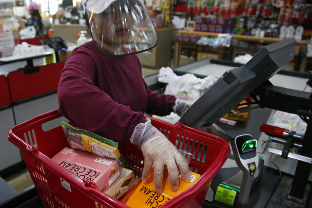 Cashier Baby San wears a face shield and gloves as she scans items at grocery store Super Cao Nguyen, Friday, March 27, 2020, in Oklahoma City, due to concerns over the COVID-19 virus. (AP Photo/Sue Ogrocki)