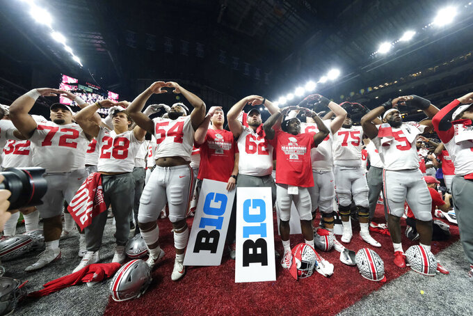 FILE - In this Dec. 8, 2019, file photo, Ohio State players celebrate the team's 34-21 win over Wisconsin in the Big Ten championship NCAA college football game, in Indianapolis. The Big Ten athletic directors support removing the conference's six-game minimum requirement for teams to be eligible to play for the league championship, and a vote is expected Wednesday, Dec. 9, 2020, to make it official. Removing the minimum would clear the way for No. 3 Ohio State to play in the Big Ten championship game on Dec. 19 against No. 15 Northwestern. (AP Photo/AJ Mast, File)