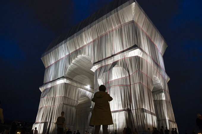 """A woman passes by the wrapped Arc de Triomphe monument on Saturday, Sept. 18, 2021, in Paris. The """"Arc de Triomphe, Wrapped"""" project by late artist couple Christo and Jeanne-Claude is on view until Oct. 3. Visitors to the famous Napoleonic arch, which dominates the Champs-Elysees Avenue, will not only be able to see the gleaming silver and blue fabric, but to touch it too — as the artists had intended. (AP Photo/Lewis Joly)"""